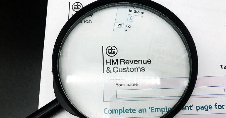 HMRC logo under a magnifying glass
