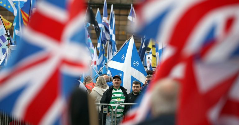 Scots with Saltires looking at a couple of Union Flags in the distance